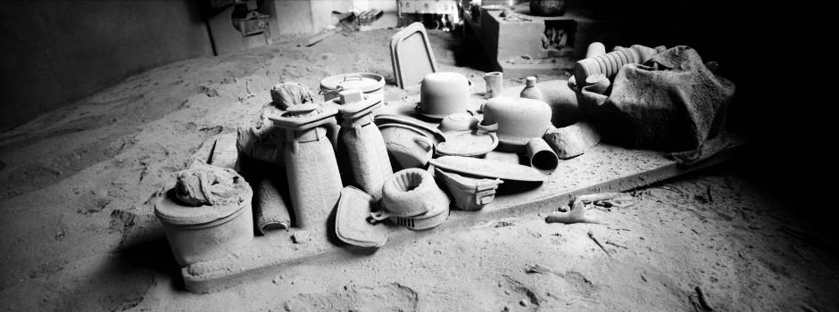 Dieses Bild zeigt von Vulkanasche bedeckte Küchenutensilien in einem zerstörten Zuhause.