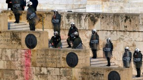 Police in riot gear stand guard outside the parliament in Athens' Syntagma square during a huge anti-austerity demonstration