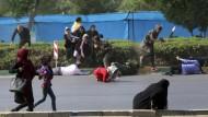 Zivilisten gehen bei einem Anschlag im Iran in Deckung.