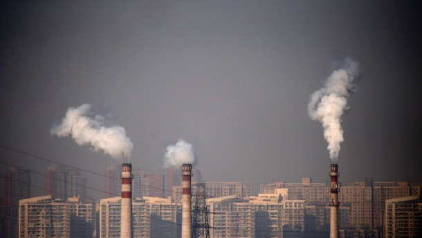 Smoking chimneys are seen in front of residential buildings in Tianjin