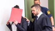 Die Angeklagte Jennifer W. hält sich beim Betreten des Gerichtssaals einen roten Aktendeckel vor ihr Gesicht. Rechts steht ihr Anwalt Ali Aydin.