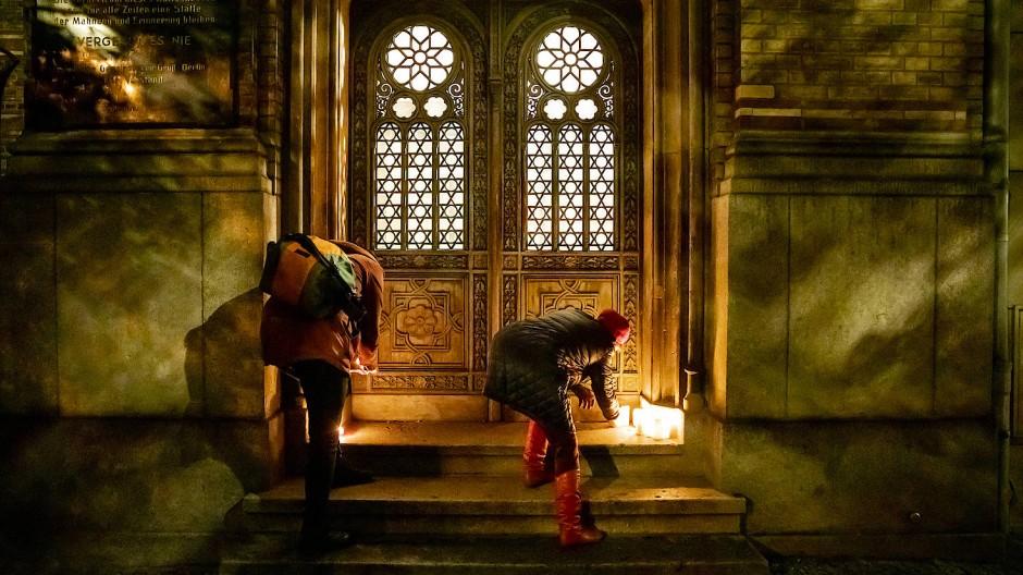 Nach dem Anschlag in Halle: Zwei Frauen stellen am 9. Oktober 2019 Kerzen auf eine Türschwelle der Neuen Synagoge in Berlin.