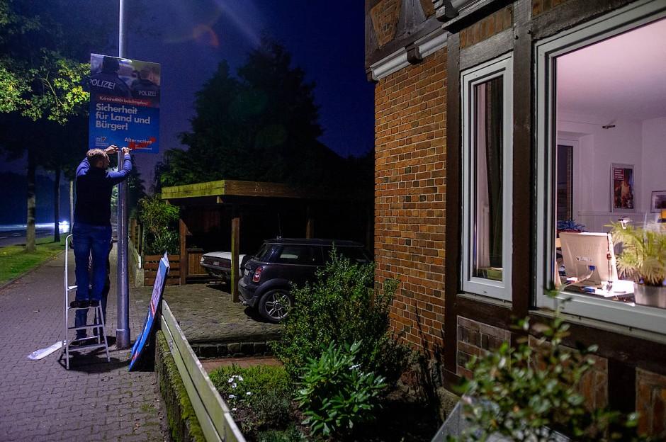 Nachts kommt die AfD: Stephan Bothe zurrt ein Plakat fest – und schiebt es dann so hoch er kann.