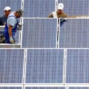 Definitiv eine grüne Investition: Arbeiter montieren bei Wallersdorf Solarmodule eines Solarfeldes.