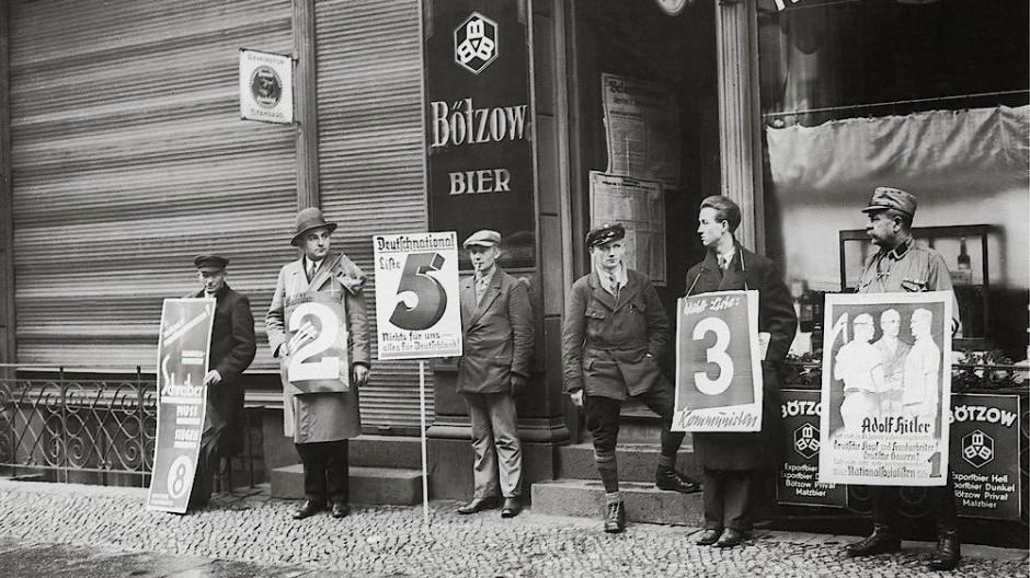Berlin am 6. November 1932:  Für die Reichstagswahl in Berlin stellen Parteien vor den Wahllokalen Vertreter mit Plakaten auf.