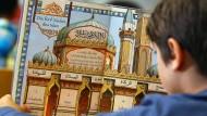 Ein Junge liest während des islamischen Religionsunterrichts in einem Schulbuch. (Symbolbild)