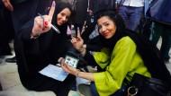 Zwei iranische Frauen bei der Stimmabgabe für die Parlamentswahlen in Teheran. Die Tinte am Finger zeigt an, dass sie gewählt haben.