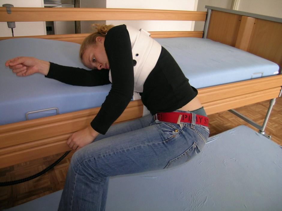 Gefahr des Bauchgurts: Der Fixierte – hier eine Mitarbeiterin der Universität München – rutscht aus dem Bett und stranguliert sich