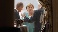 Gleich geht's los: Angela Merkel spricht am Sonntagmorgen mit Donald Tusk (l.) und Boris Johnson.