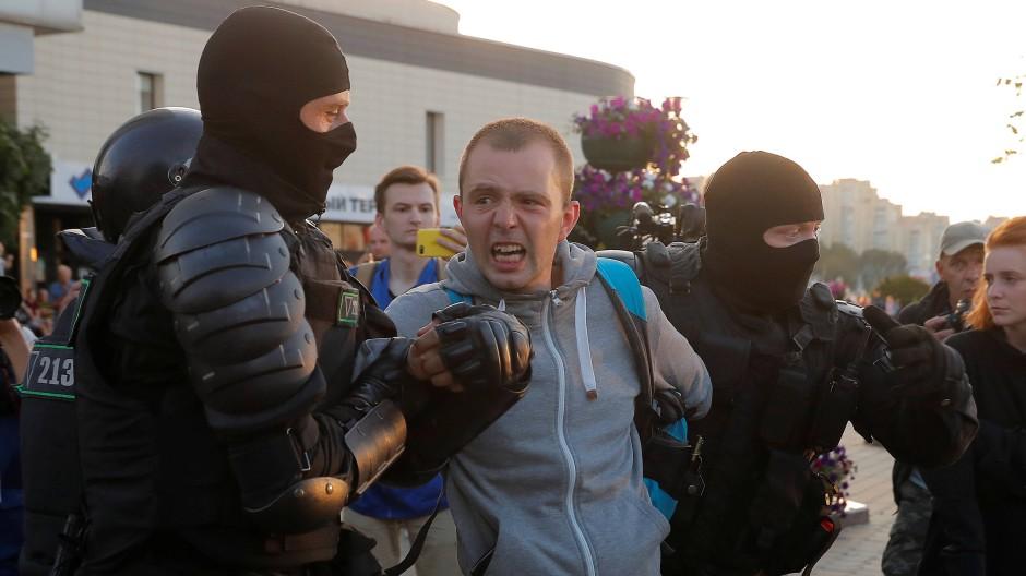 Sicherheitskräfte nehmen einen Mann in Minsk fest.