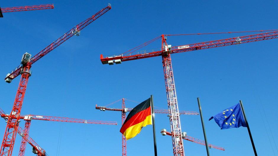 Die europäische und die deutsche Flagge zwischen Baukränen im Berliner Regierungsviertel: Die deutsche Wirtschaft hofft auf ein Ende der politischen Hängepartie.