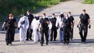 Polizisten und Umweltaktivisten verlassen das abgesperrte Gelände der A100 an der Sonnenallee in Berlin.