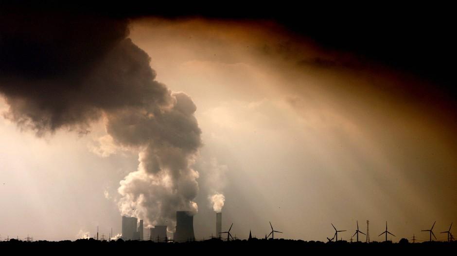 Fossil und erneuerbar: Windräder und das Braunkohlekraftwerk Niederaußem bei Bergheim in Nordrhein-Westfalen.