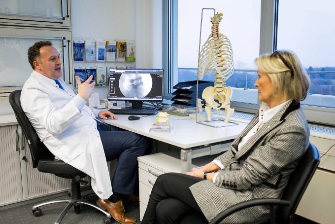 Der Wirbelsäulenchirurg Frank Kandziora erklärt Patientin Martha Bell am Modell und mit Bildern, wie er ihren Rücken wieder gerichtet hat.