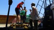 """Die Crew verstaut Wasservorräte an Deck der """"Alan Kurdi""""."""