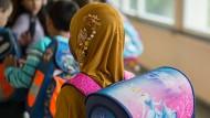 Ein Mädchen mit Kopftuch steht in einer Schule vor einem Klassenzimmer.