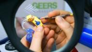Eine Geers-Hörgeräteakustikerin bearbeit unter einer Lupe ein Hörgerät für Kinder.