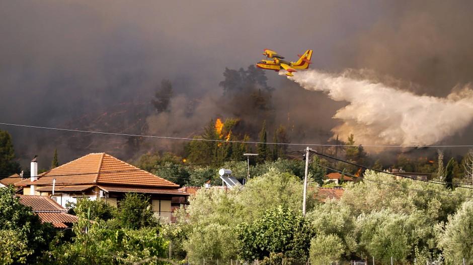 Ein Flugzeug wirft Wasser ab, um das Dorf Olympia und die antiken Stätten vor dem sich ausbreitenden Waldbrand zu schützen.