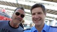Arnold Schwarzenegger und Polizeioberkommissar Stefan Schmitt am Samstag in München.