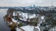 Die Parkanlagen an der Außenalster sind Montag in Hamburg noch mit einer Schneeschicht überzogen.