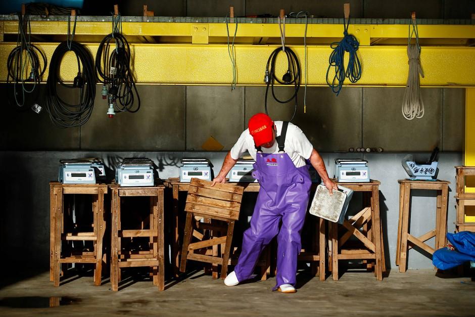 Ein Fischer bereitet einen Hocker und eine Waage vor, um die Körbe mit Fisch auf dem Fischmarkt zu wiegen.