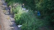 Polizeibeamte gehen an einer Bahnstrecke nahe Wiesbaden-Erbenheim entlang auf dem Weg zu einem Leichenfundort in einem Gebüsch.