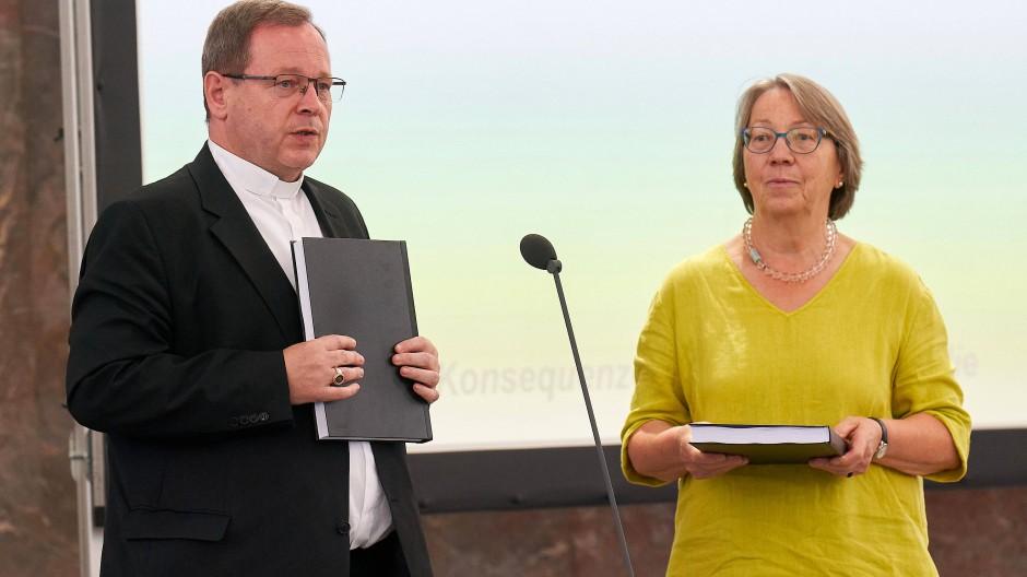 """In der Frankfurter Paulskirche: Der Limburger Bischof Georg Bätzing hält den Bericht des Projekts """"Betroffene hören - Missbrauch verhindern"""" in der Hand. Rechts neben ihm  Ingeborg Schillai, die die Studie in Auftrag gegeben hatte."""