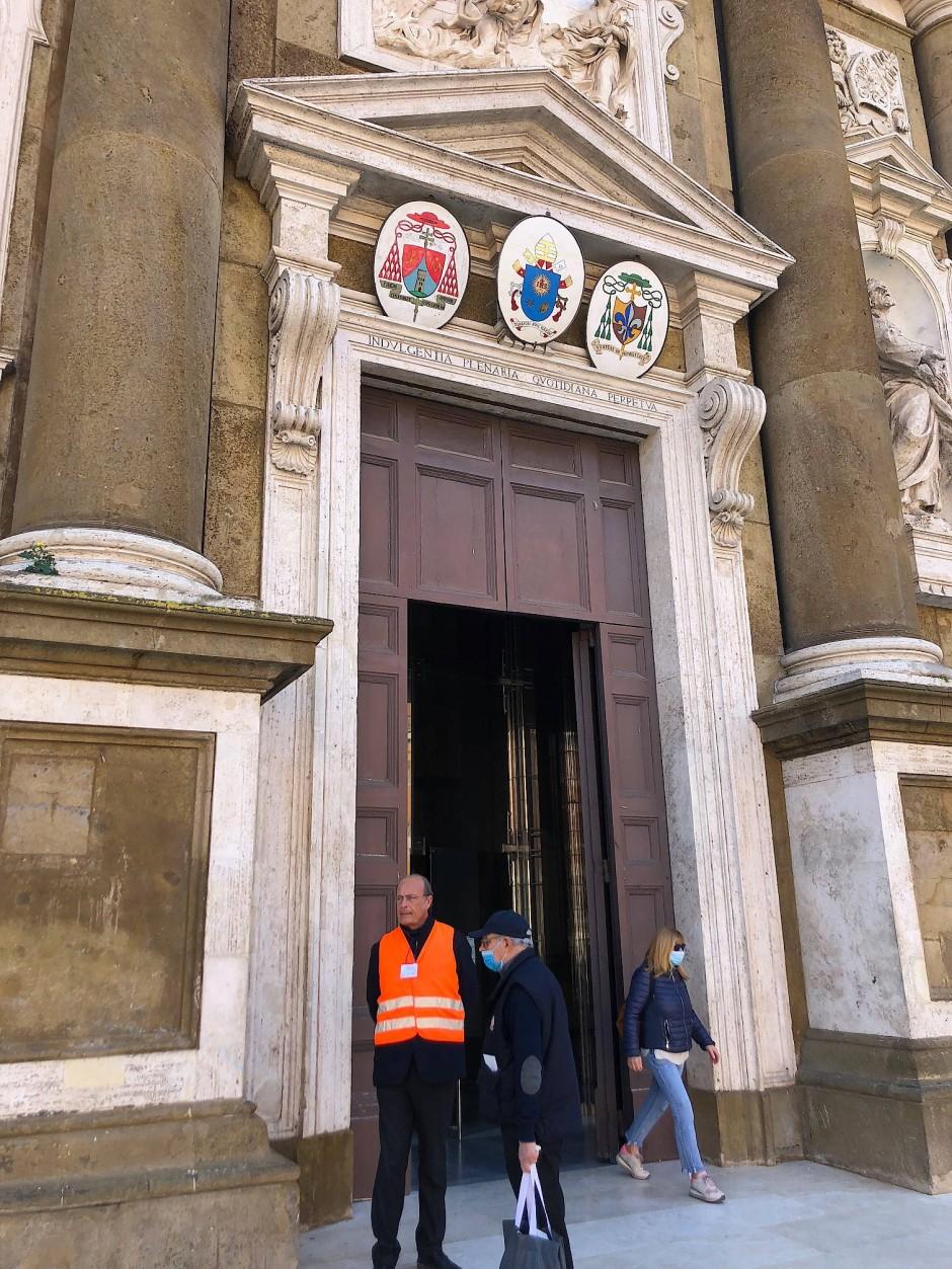Wächter in orange: Ein Kirchenmitarbeiter achtet auf die Zahl der Anwesenden.