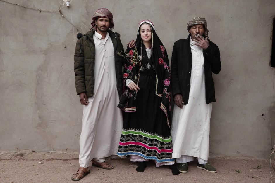 Eine ägyptische Studentin hat sich ein beduinisches Hochzeitskleid geliehen, um sich mit Männern aus dem Stamm von Umm Yasser fotografieren zu lassen.