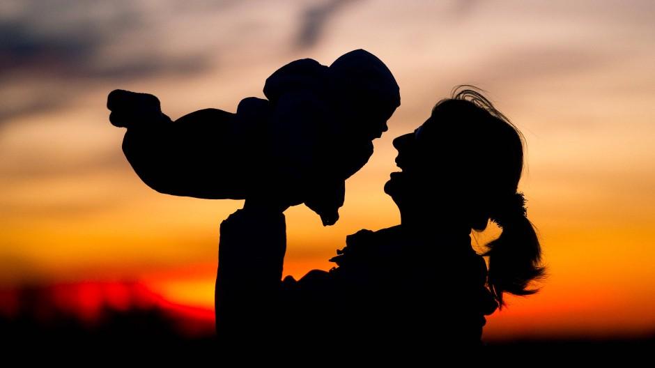 Eine Mutter hebt ihr Baby in die Luft (Symbolbild).