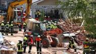 Einsatzkräfte räumen in Rettenbach Schutt beiseite. Eine Explosion hat hier ein Wohnhaus zerstört.