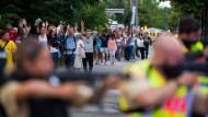 Augenzeugen verlassen am Freitagabend mit erhobenen Händen das Einkaufszentrum in München.