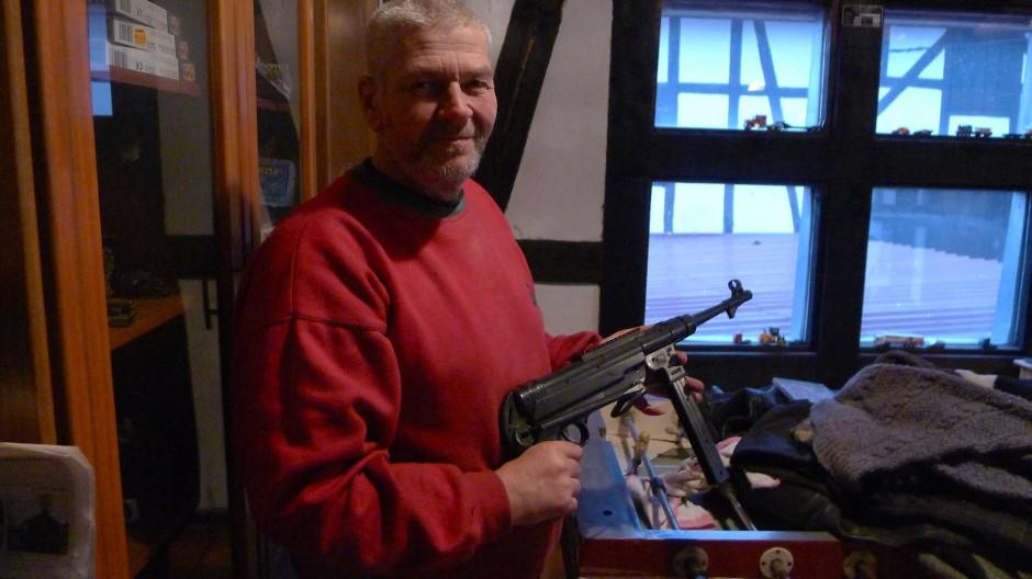 Bertram Köhler ist 56 Jahre alt. Er lebt im hessischen Kirtorf. Für unser Bild zeigt er seine Spielzeugmaschinenpistole. Auf seinem Hof lagert er Hunderte alte NPD-Plakate.