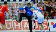 Polens Torhüter Slawomir Szmal sichert den knappen Sieg: Er hält den Ball von Ivan Nikcevic.