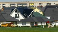 Mehrere Einfamilienhäuser stehen am Stadtrand vor Bauten der Plattenbausiedlung Neu Olvenstedt in Magdeburg.