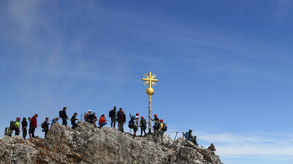 Am Gipfelkreuz der Zugspitze treffen Sonntagsausflügler auf Bergprofis, die über den schmalen Jubiläumsgrat geklettert kommen.