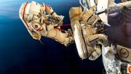 Zwei Kosmonauten überprüfen ein Leck an einer Raumkapsel.