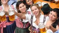 Besucherinnen in Tracht prosten sich mit ihren Bierkrügen zu.