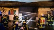 Ausgebrannt: Feuerwehrleute löschen in den frühen Morgenstunden einen Großbrand in einem Baumarkt in Limburg.