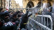 Demonstranten versuchen in Beirut bei Protesten in der Nähe des Parlaments mit einem Teil einer Straßenabsperrung Sicherheitskräfte zurückzudrängen.