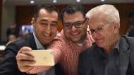 Cem Özdemir und Winfried Kretschmann machen ein Selfie mit dem Delegierten Sahin Karaaslan beim Grünen-Parteitag.