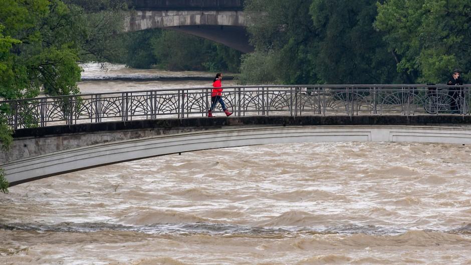 Starke Strömung: Ein Passant geht über einen Steg, der über die Isar führt.