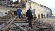 Kroatien, Petrinja: Menschen in den Trümmern eines vom Erdbeben beschädigten Gebäudes