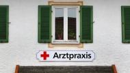Ein Schild an einem Haus weist in der kleinen Gemeinde auf eine Arztpraxis hin.