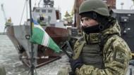 Ein Soldat auf einem ukrainischen Küstenwachtschiff im Hafen von Mariupol