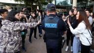 Im Konflikt: Polizisten trennen Peking-Gegner und -Anhänger in Adelaide.