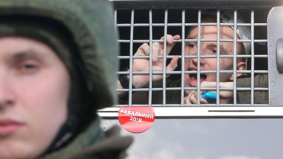 Ein festgenommener Demonstrant blickt aus einem Polizeifahrzeug in Moskau.