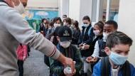 Ein Schulmitarbeiter verteilt im November 2020 Handdesinfektionsmittel an Schüler in Antibes.