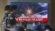 In Südkoreas Hauptstadt Seoul sehen Passanten, darunter auch Soldaten, einen Bericht zum jüngsten Raketentest des Nordens.