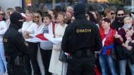 """Mit Blumen gegen die Maskenmänner des Staates: Protestierende Belarussinnen singen das Lied """"Kupalinka""""."""